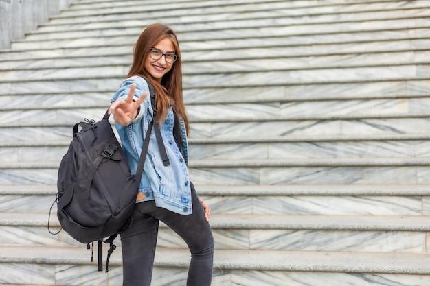 Młoda wesoła kobieta studentka w dżinsowej kurtce i okularach z dużym plecakiem wspina się po schodach w mieście. koncepcja młodzieży