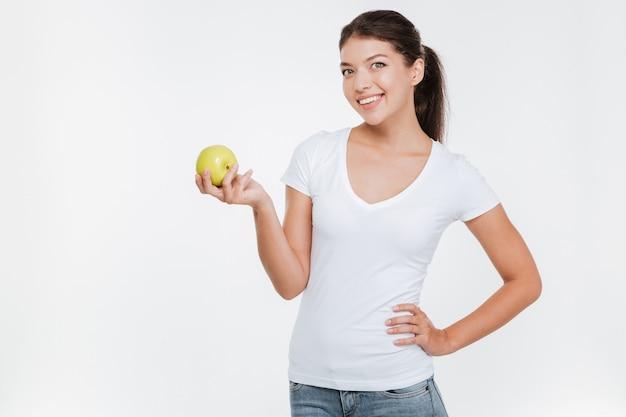 Młoda wesoła kobieta trzyma jabłko na białej ścianie