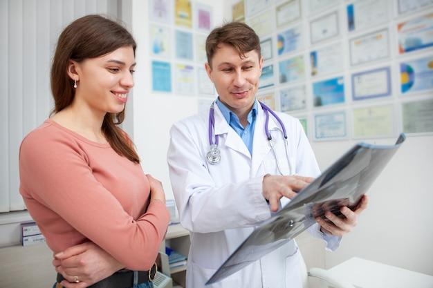 Młoda wesoła kobieta uśmiechnięta, otrzymująca dobre wieści od swojego lekarza po skanowaniu mri