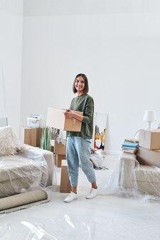 Młoda wesoła kobieta w codziennym noszeniu pudełka z rzeczami, poruszając się po salonie nowego mieszkania lub domu