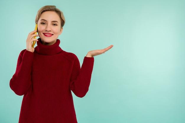 Młoda wesoła kobieta w czerwonym swetrze ze smartfonem na niebieskim tle