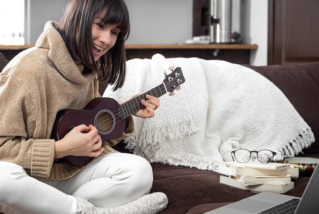 Młoda wesoła kobieta w swetrze uczy się gry na ukulele. koncepcja uczenia się online, edukacja domowa.