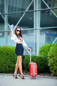 Młoda wesoła kobieta z walizką.