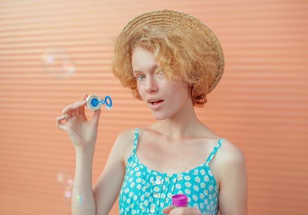 Młoda wesoła kręcona ruda kobieta w niebieskiej sukience i słomkowym kapeluszu z bąbelkami na beżowym tle