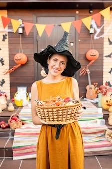 Młoda wesoła ładna kobieta w czarnym kapeluszu halloween wiedźma trzymająca kosz ze słodyczami, czekając na halloweenowe dzieci przy udekorowanych drzwiach