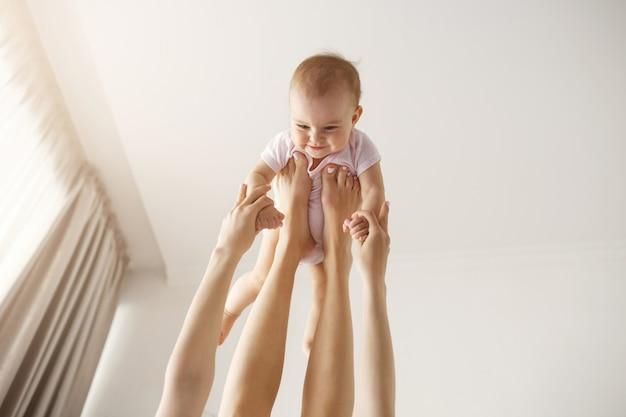 Młoda wesoła matka bawi się z jej noworodkiem, leżąc na łóżku w domu