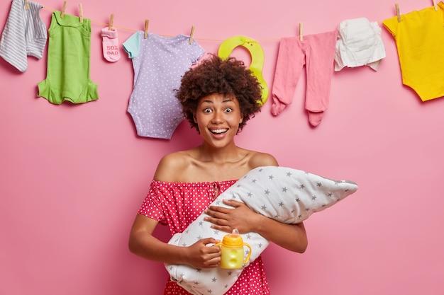 Młoda wesoła matka karmiąca piersią, pozuje z nowonarodzonym chłopcem, karmi dziecko, cieszy się życiem, spędza czas w domu, dba o malucha, stoi przy różowej ścianie z ubraniami dla dzieci wiszącymi na linie