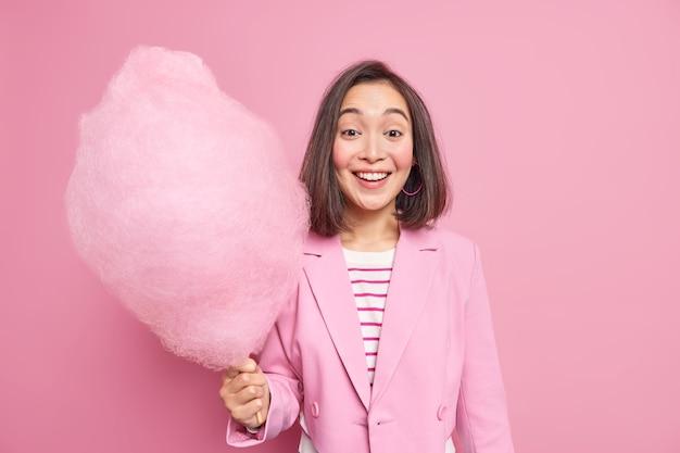 Młoda, wesoła młoda kobieta o wschodnim wyglądzie, uśmiecha się z wielką watą cukrową, będąc w dobrym nastroju, ubrana w modne ubrania pozytywna azjatycka kobieta trzyma słodki deser na patyku