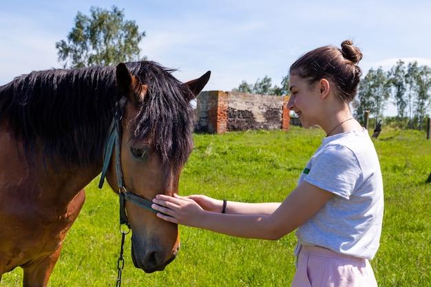 Młoda wesoła nastolatka głaszcząc nos brązowy konia