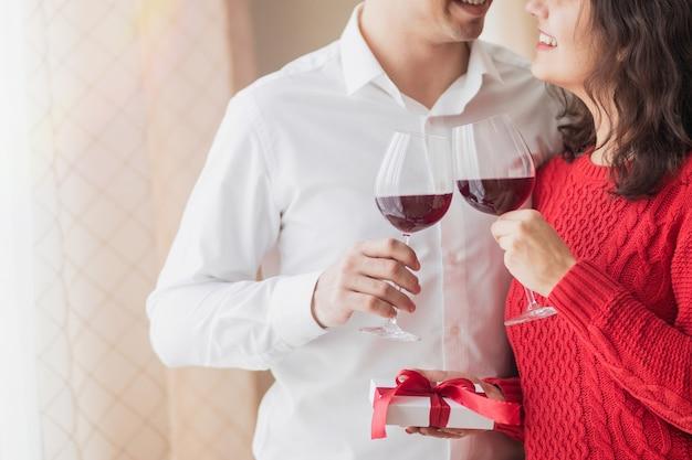Młoda wesoła para uśmiecha się do siebie, pije wino i trzyma mały biały prezent z czerwoną wstążką w rękach w restauracji. koncepcja walentynki.
