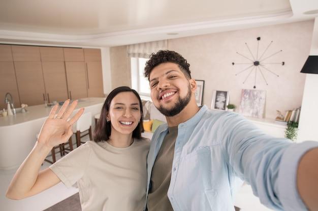 Młoda wesoła para w casualowym stroju, patrząca na ciebie z zębami, stojąc przed kamerą i robiąc selfie w domu