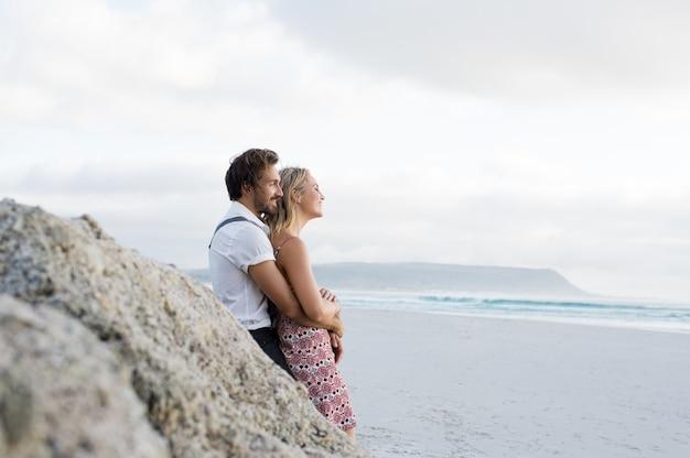 Młoda wesoła para zakochanych, opierając się na skale i patrząc na morze