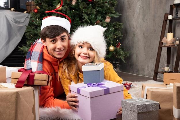 Młoda wesoła para zakochanych pozowanie z prezentami na boże narodzenie w salonie.