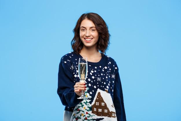 Młoda wesoła piękna brunetka dziewczyna w przytulny sweter z dzianiny uśmiechnięty, trzymając kieliszek szampana na niebieską ścianą