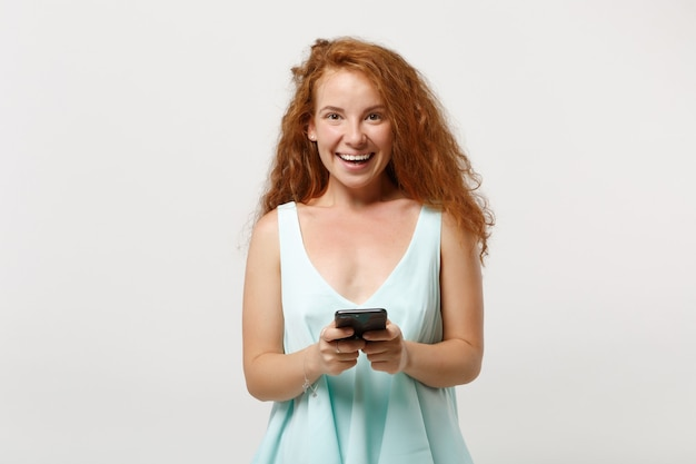 Młoda wesoła ruda kobieta dziewczyna w dorywczo lekkie ubrania pozowanie na białym tle na białym tle, portret studio. koncepcja życia ludzi. makieta miejsca na kopię. używając telefonu komórkowego, wpisując wiadomość sms.