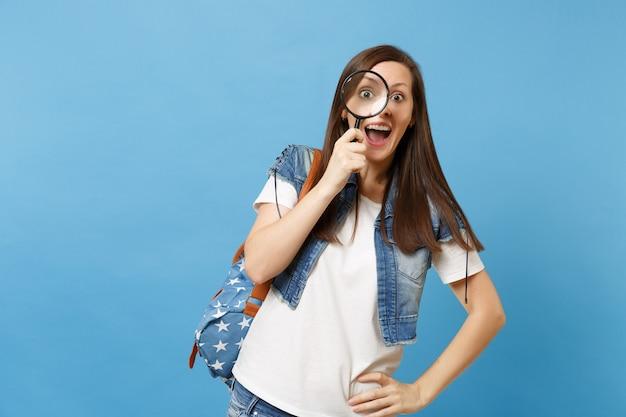 Młoda wesoła zdumiona kobieta studentka w dżinsowe ubrania z plecakiem patrząc przez szkło powiększające, ucząc się i badając na białym tle na niebieskim tle. edukacja w liceum ogólnokształcącym.