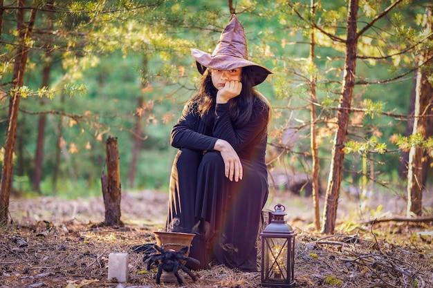 Młoda wiedźma w kapeluszu siedzi na pniu w lesie, z głową podpartą ręką, smutna.