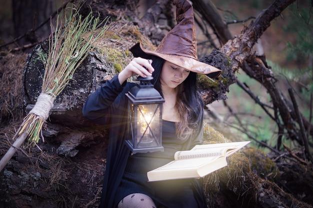Młoda wiedźma w lesie siedzi na pniu, czyta książkę i oświetla ją zabytkową lampą.