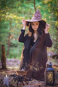Młoda wiedźma w lesie siedzi na pniu, trzymając się kapelusza.