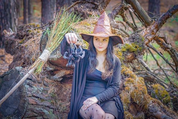 Młoda wiedźma w lesie siedzi na pniu, trzymając za łapę dużego pająka.