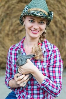 Młoda wiejska dziewczyna rolnik w koszuli i kapelusz cowgirl. trzymając królika i uśmiechając się