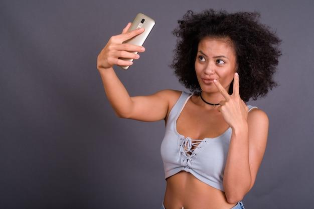 Młoda wieloetniczna african american kobieta z afro włosy przed szarej ścianie
