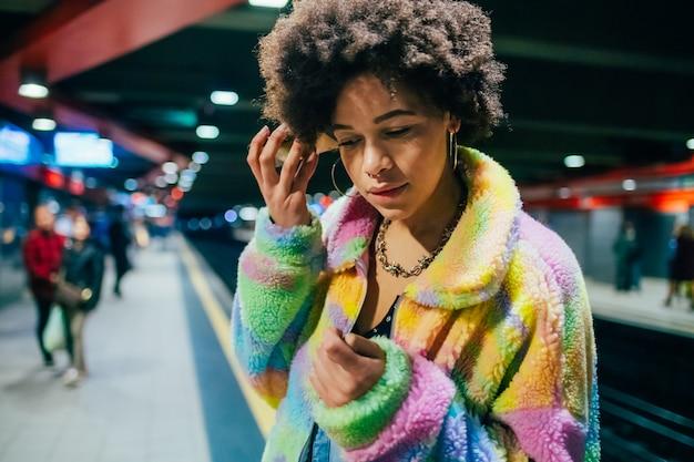 Młoda wieloetniczna kobieta pod ziemią przy użyciu telefonu słuchania wiadomości głosowej