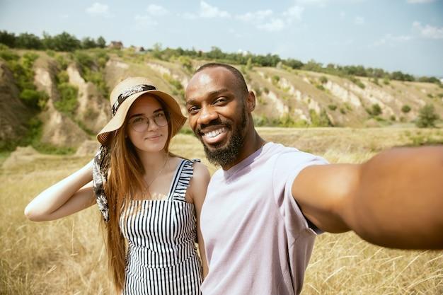 Młoda wieloetniczna międzynarodowa para na zewnątrz na łące w słoneczny letni dzień. afro-mężczyzna i kaukaski kobieta razem piknik. pojęcie związku, czas letni. robię selfie.