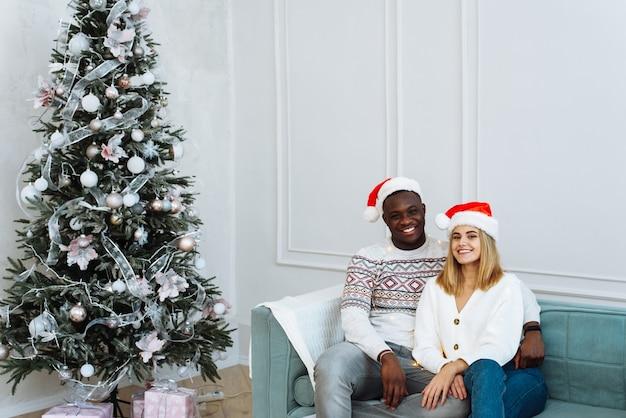 Młoda wieloetniczna para w czapkach mikołaja siedzi na sofie w jasnym wnętrzu obok drzewa