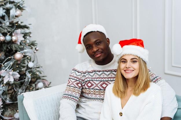 Młoda wieloetniczna para w mikołajowych czapkach siedzi na kanapie w jasnym wnętrzu obok drzewa. mężczyzna i kobieta patrząc w kamerę, uśmiechając się.