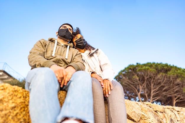 Młoda, wielorasowa para zakochanych siedzi na ścianie, nosząc czarną bezpieczną maskę ochronną na twarz, patrząc na horyzont o zachodzie słońca. globalna pandemia zaburzająca normalne życie i przyszłość ludzi