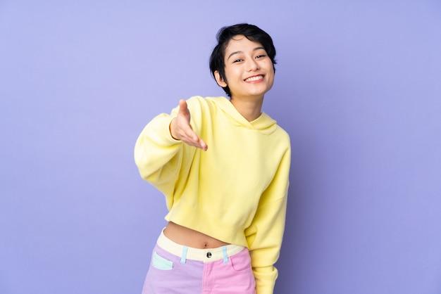 Młoda wietnamka z krótkimi włosami na fioletowych ścianach, drżącymi rękami za zamknięcie dobrego interesu