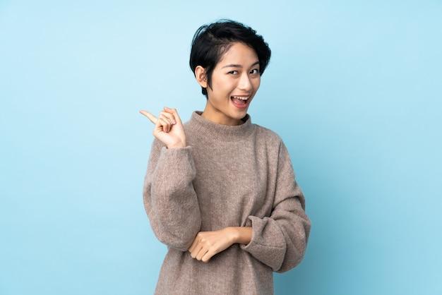 Młoda wietnamka z krótkimi włosami na izolowanej ścianie, zamierzająca zrealizować rozwiązanie, jednocześnie podnosząc palec