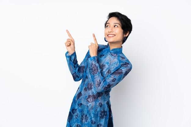 Młoda wietnamka z krótkimi włosami ubrana w tradycyjną sukienkę na białej ścianie izolowanej wskazująca palcem wskazującym świetny pomysł