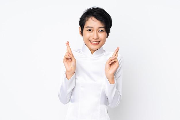 Młoda wietnamka z krótkimi włosami ubrana w tradycyjną sukienkę na białej ścianie ze skrzyżowanymi palcami i życzącymi wszystkiego najlepszego