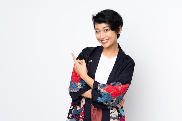 Młoda wietnamka z krótkimi włosami ubrana w tradycyjny strój na izolowanej białej ścianie skierowana w bok, aby przedstawić produkt