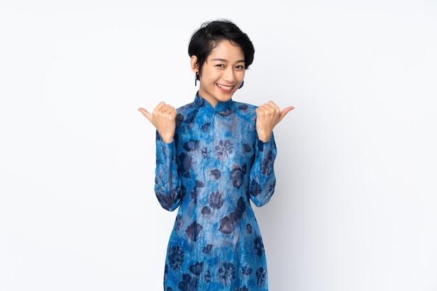 Młoda wietnamska kobieta z krótkim włosy jest ubranym tradycyjną suknię nad odosobnioną biel ścianą z aprobatami gestykuluje i ono uśmiecha się