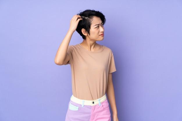 Młoda wietnamska kobieta z krótkim włosy nad odosobnioną purpury ścianą ma wątpliwości podczas gdy drapający głowę