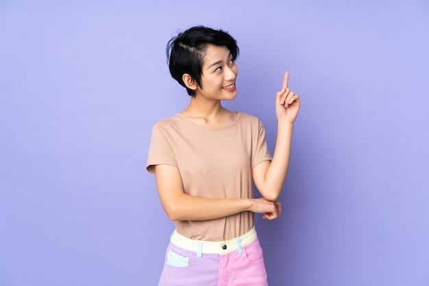 Młoda wietnamska kobieta z krótkim włosy nad odosobnioną purpury ścianą wskazuje w górę doskonałego pomysłu