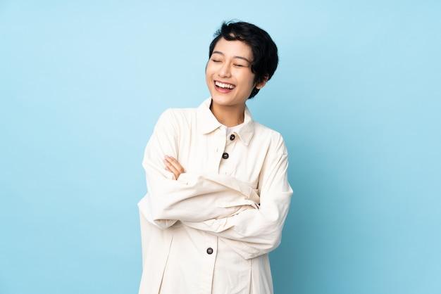 Młoda wietnamska kobieta z krótkim włosy nad odosobnioną ścianą szczęśliwą i uśmiechniętą