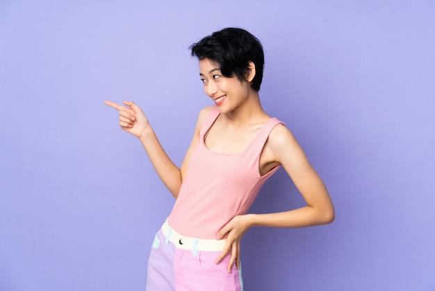Młoda wietnamska kobieta z krótkim włosy nad odosobnionym purpurowym ściennym wskazuje palcem z boku i przedstawia produkt
