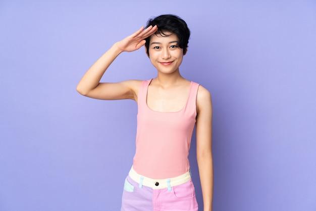 Młoda wietnamska kobieta z krótkim włosy nad odosobnionymi purpurami izoluje salutować ręką z szczęśliwym wyrażeniem
