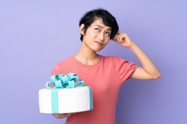 Młoda wietnamska kobieta z krótkim włosy trzyma dużego tort na odosobnionych purpurach ma wątpliwości i z zmieszanym wyrazem twarzy