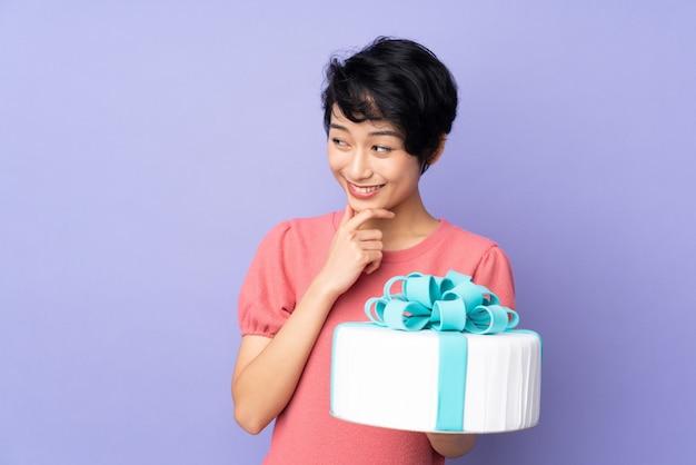 Młoda wietnamska kobieta z krótkim włosy trzyma duży tort nad purpurową ścianą myśląc pomysł i patrząc z boku