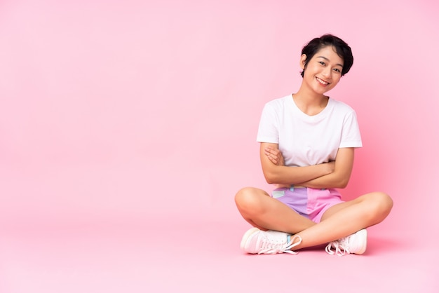 Młoda wietnamska kobieta z krótkimi włosami siedzi na podłodze nad izolowaną różową ścianą, trzymając ręce skrzyżowane w pozycji frontalnej