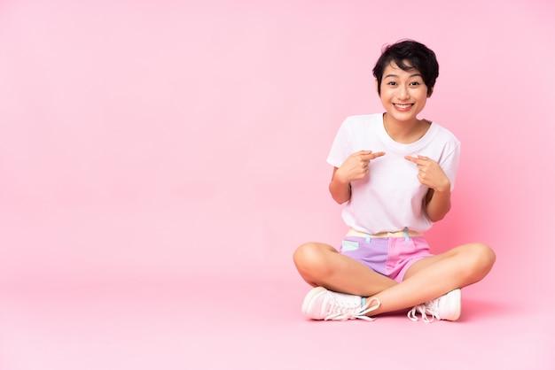 Młoda wietnamska kobieta z krótkimi włosami siedzi na podłodze nad różową ścianą z zaskoczonym wyrazem twarzy