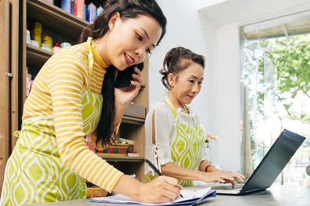 Młoda wietnamska kwiaciarka rozmawia przez telefon z klientem i robi notatki w dokumencie, gdy jej współpracownik sprawdza zamówienia za pośrednictwem strony internetowej