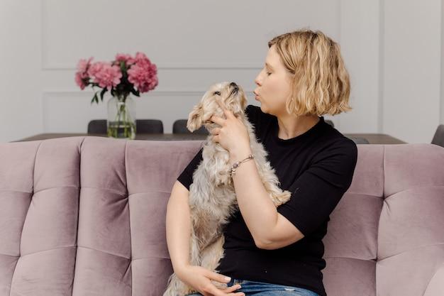 Młoda właścicielka przytula i całuje swojego pupila yorkshire terriera.