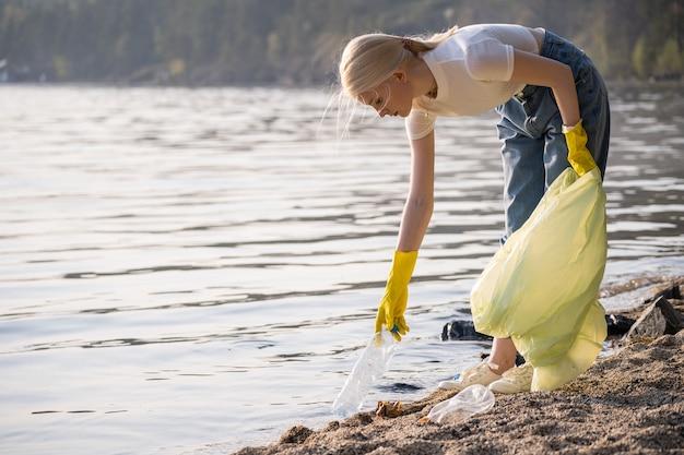 Młoda wolontariuszka w gumowych rękawiczkach z plastikową torbą sprząta śmieci na brzegu jez...