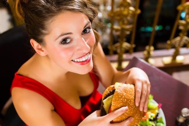 Młoda womana wyśmienita restauracja je hamburgera, zachowuje się niewłaściwie